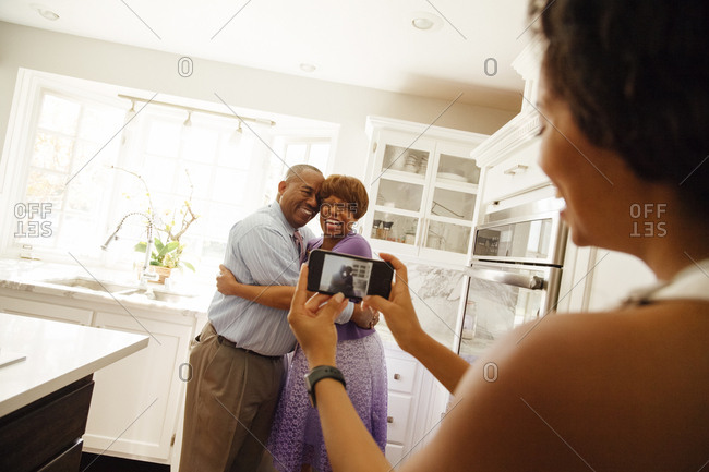 Woman photographing parents embracing each other through smartphone in kitchen