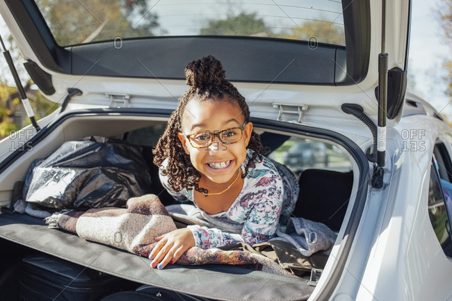 Portrait of smiling girl in car trunk