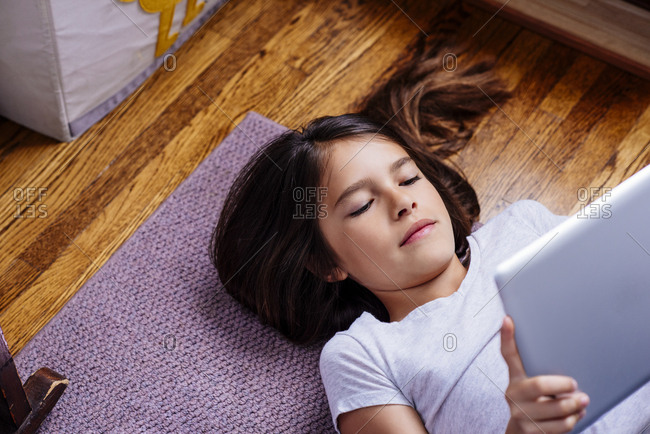 High angle view of girl using digital tablet while lying on floor at home