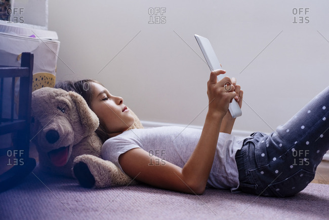 Side view of girl using digital tablet while lying on rug in bedroom