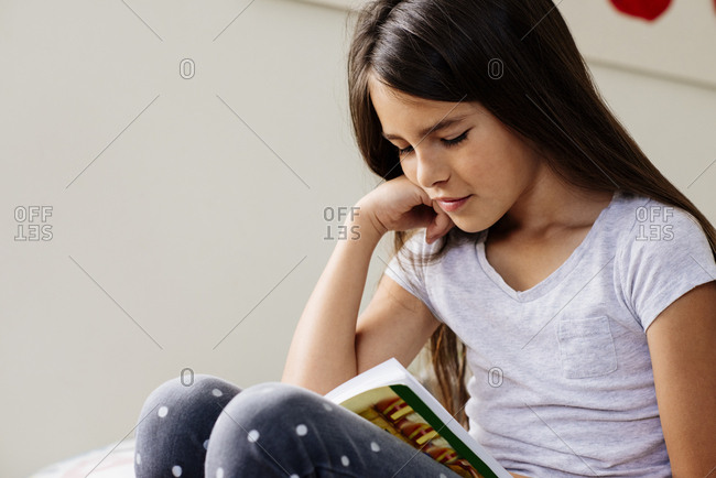 Young girl read book in bedroom