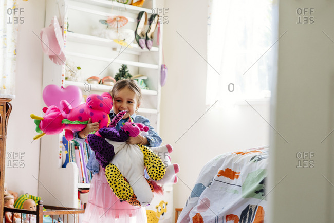 Cute girl looking away while carrying multiple toys in brightly lit bedroom