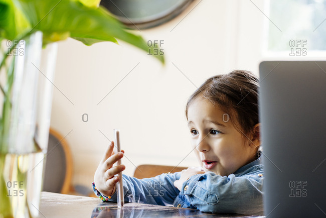 Surprised girl using smartphone while sitting at table at home