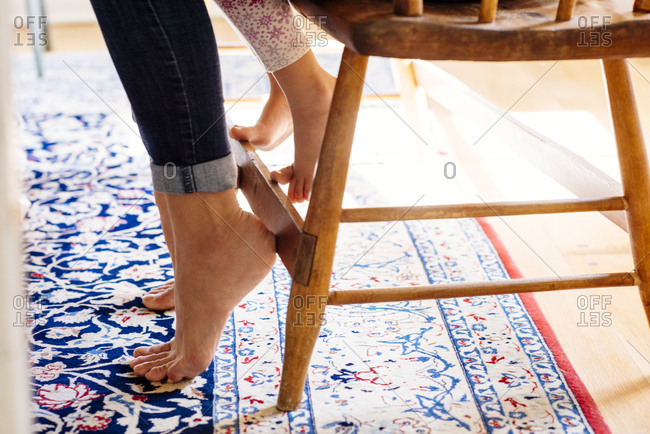 Low angle of mother and daughter sitting on wooden chair