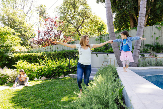 Mother helping daughter balance while walking along edge of pool