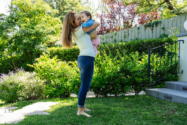 Full length side view of cheerful woman carrying daughter at yard