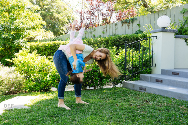 Full length of playful woman carrying daughter upside down at yard