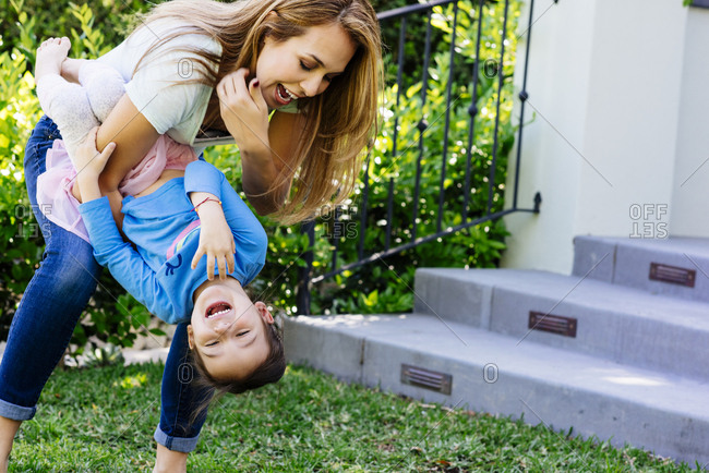 Playful mid adult mother carrying daughter upside down at yard