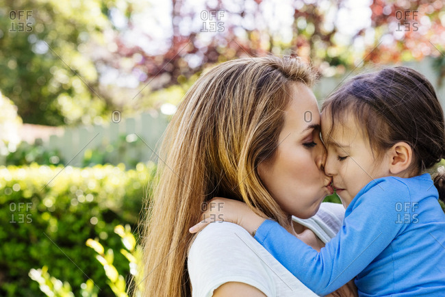 Side view of loving mid adult mother kissing daughter at yard