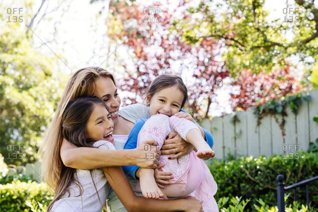 Playful mid adult woman embracing daughters at yard during sunny day