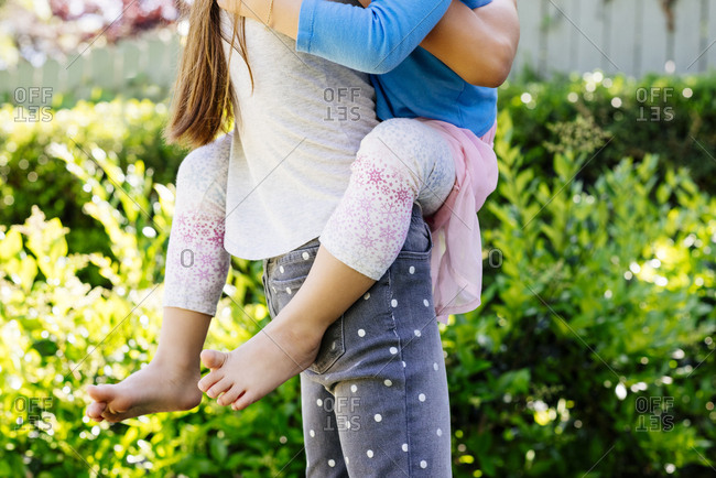 Midsection of girl carrying sister while standing at yard