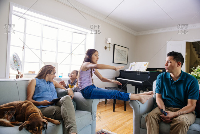 Happy family of four spending leisure time in living room at home