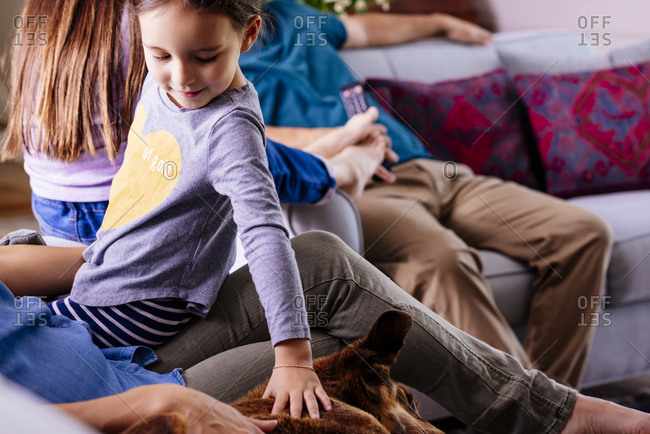 Cute girl petting dog lying on sofa while sitting with mother at home