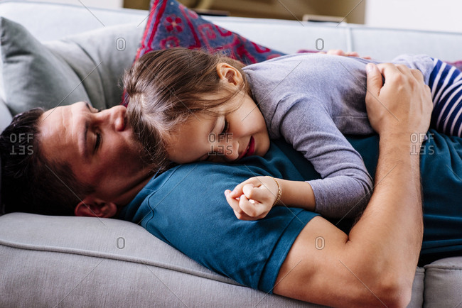 Side view of cute girl lying on father in living room at home