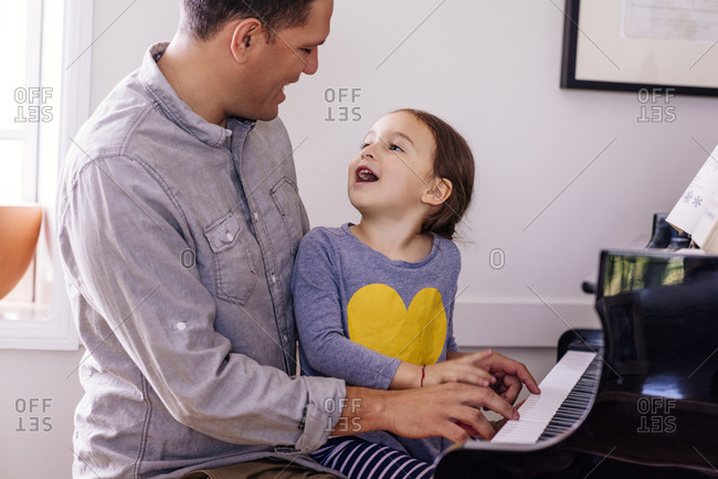 Cute girl talking to father playing grand piano at home