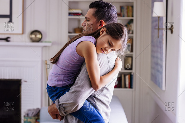 Side view of father carrying daughter at home