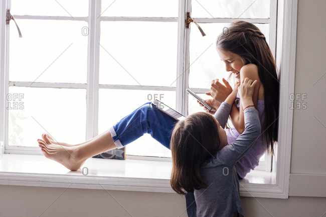 Rear view of girl tickling sister sitting with smartphone and digital tablet on window sill at home