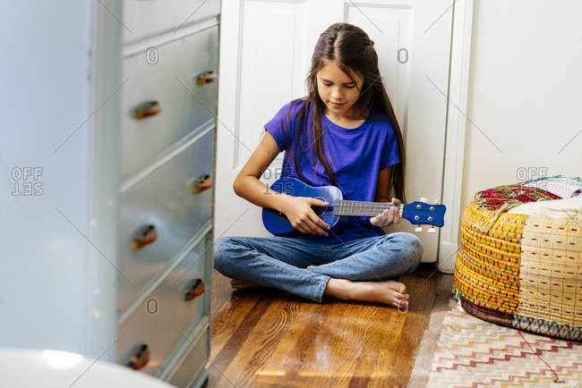 Full length of girl playing toy guitar while sitting on hardwood floor at home