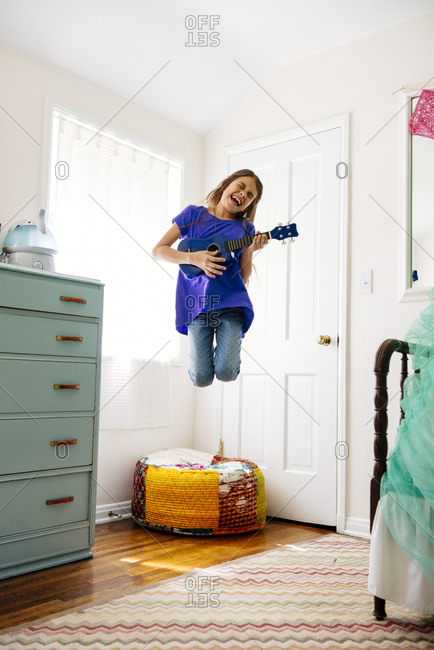 Excited girl jumping while playing toy guitar at home