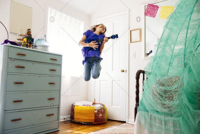 Excited girl jumping while playing toy guitar at brightly lit home