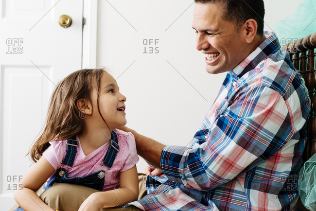 Cheerful mid adult father talking to daughter at home
