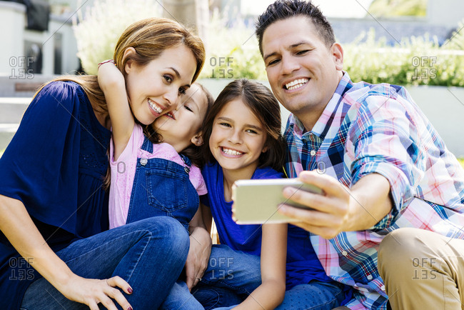 Happy man taking selfie through smartphone with family while sitting at yard