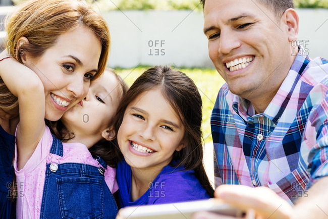 Happy mid adult man taking selfie through smartphone with family while sitting at yard