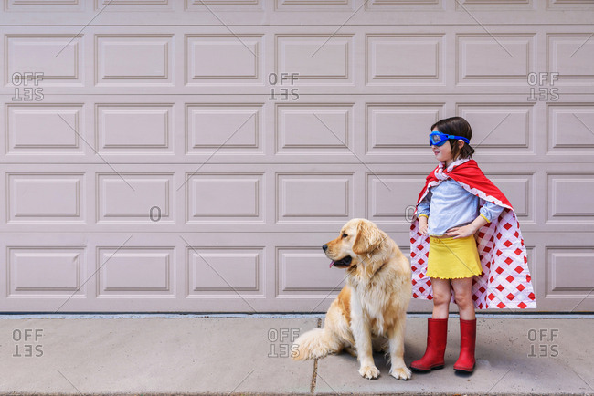 Young girl in super hero cape outside with dog