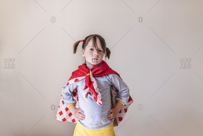 Young girl in a super hero cape and mask