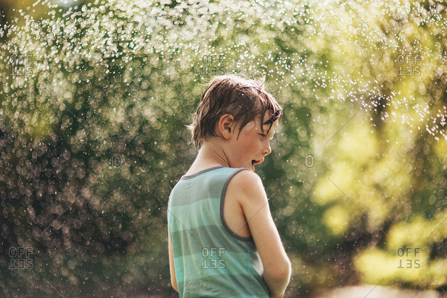 Young boy playing in a sprinkler in the backyard