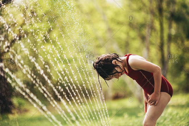 Young girl playing in a sprinkler in the backyard