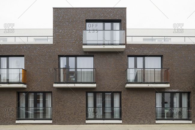 Exterior of modern brick building with windows and balconies