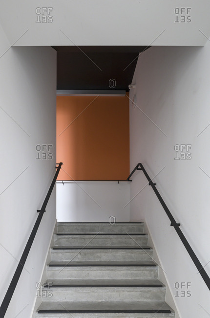 Interior stairway with one orange wall in modern office building