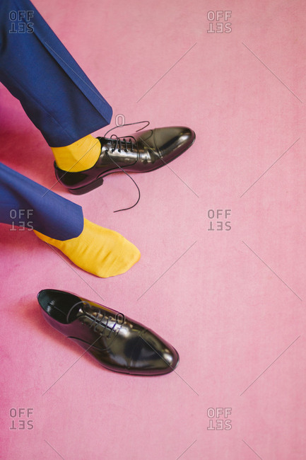 Groom in blue suit putting on shoes