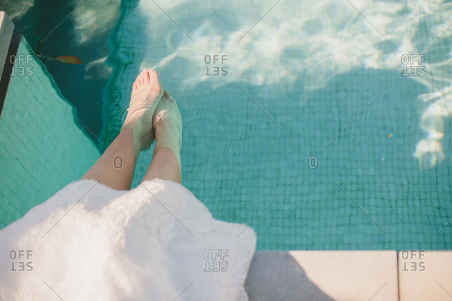 Bride with feet in pool water