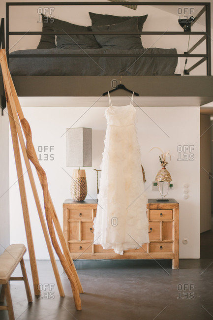 Wedding gown hanging from lofted bed