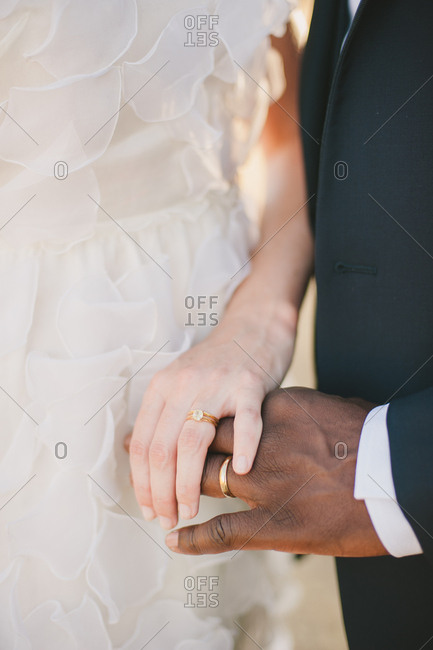 Bride and groom touching hands