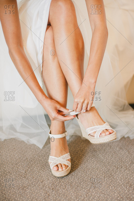 Bride strapping on her shoes