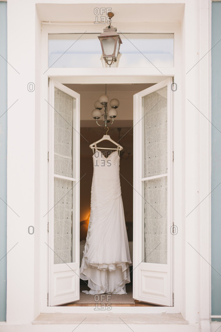Wedding dress hanging from lamp in door