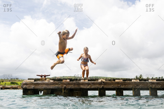 Boy (8-9) and girl (6-7) jumping into sea from jetty