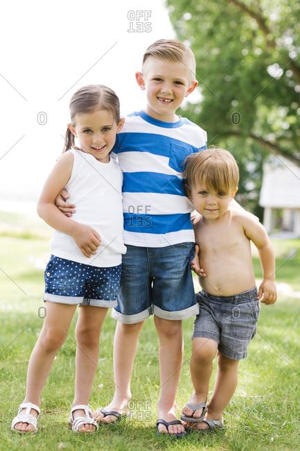 Siblings (2-3, 4-5, 6-7) embracing in park