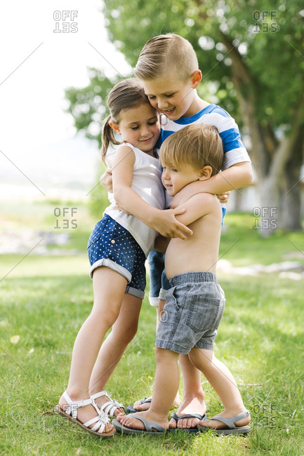 Siblings (2-3, 4-5, 6-7) embracing in park