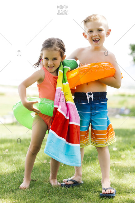 Girl (4-5) and boy (6-7) holding towel and inflatable rings