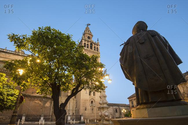 Spain, Seville, Plaza Virgin De Los Reyes, Statue and Giralda Tower at dusk
