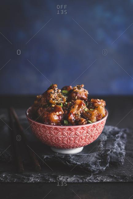 Bowl of honey garlic spareribs on a slate board