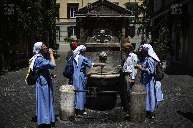 Rome, Italy - June 4, 2017: A group of nuns drinking water in the Borgo Pio district of Rome, Italy