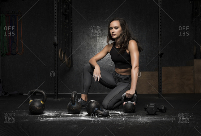 Woman kneeling on gym floor with her hand on kettlebell