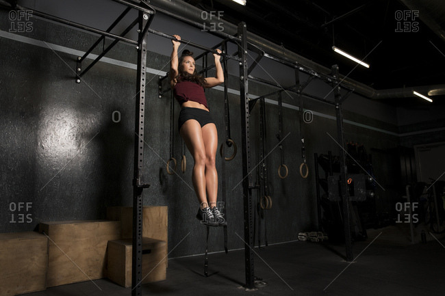 Woman doing pull-ups at the gym