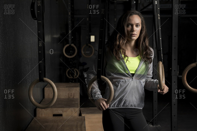 Woman holding gymnastic rings at the gym