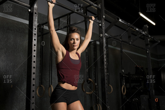 Woman holding bar while doing pull-ups at the gym